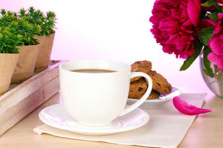 cup of coffee, cookies and flowers on table in cafe photo
