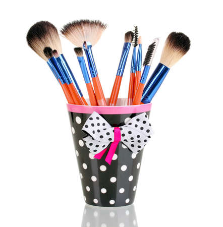 cosmetic products: Makeup brushes in a black polka-dot cup isolated on white