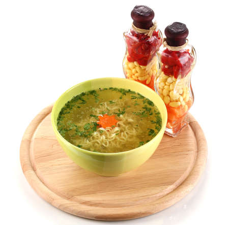 Tasty chicken stock with noodles on wooden round board isolated on white photo