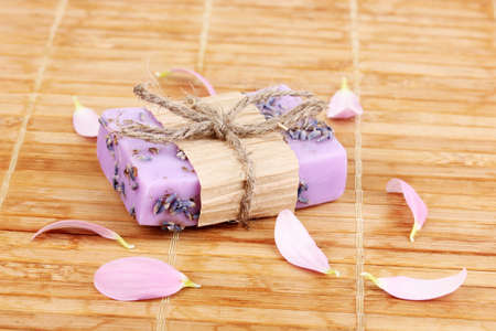 Hand-made lavender soap on wooden mat photo
