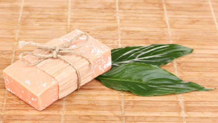 Hand-made natural soap on wooden mat photo