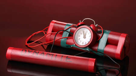 Timebomb made of dynamite on red background photo