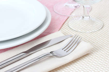 restaurant setting: Table setting with fork, knife, plates, and napkin