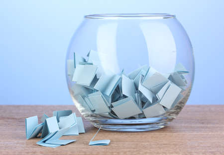raffle: Pieces of paper for lottery in vase on wooden table on blue background Stock Photo