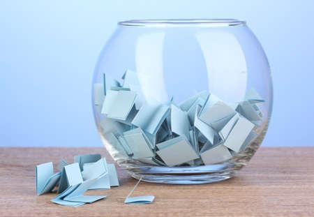 Stukken van papier voor loterij in vaas op houten tafel op een blauwe achtergrond