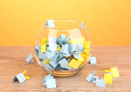 involvement: Pieces of paper for lottery in vase on wooden table on yellow background
