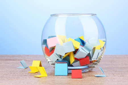 Stukken van papier voor loterij in vaas op houten tafel op een blauwe achtergrond Stockfoto