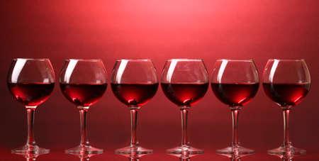 vid: Copas de vino sobre fondo rojo Foto de archivo