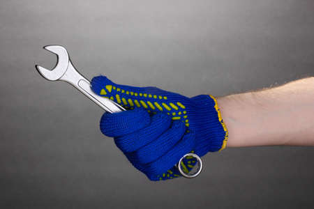 Wrench in hand with protection glove on grey background photo