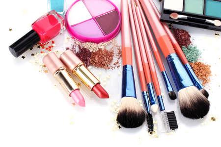 mujer maquillandose: pinceles de maquillaje y cosm�ticos en el soporte aislado en blanco
