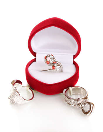 silver ring: Silver ring with red, pink and clear crystals in red velvet box and some silver rings isolated on white Stock Photo