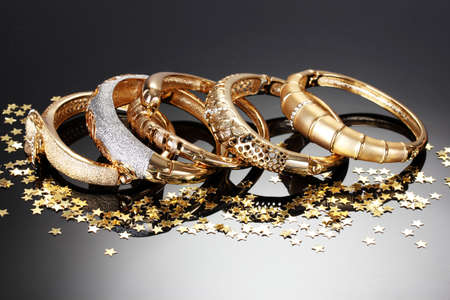 Beautiful golden bracelets on grey background Archivio Fotografico