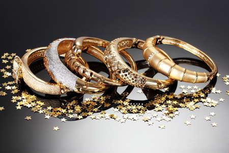 Schöne goldene Armbänder auf grauem Hintergrund