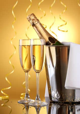 brindisi spumante: Bottiglia di Champagne in secchiello con ghiaccio e bicchieri di champagne, su sfondo giallo Archivio Fotografico