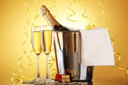 Bottiglia di Champagne in secchiello con ghiaccio e bicchieri di champagne, su sfondo giallo Archivio Fotografico