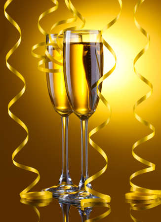 glasses of champagne and streamer on yellow background Stock Photo - 13648730
