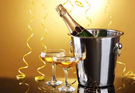 Champagne bottle in bucket with ice and glasses of champagne, on yellow background Stock Photo - 13649200