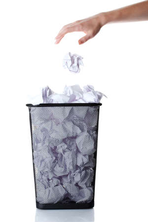 trash can: hand going garbage in metal trash bin from paper isolated on white