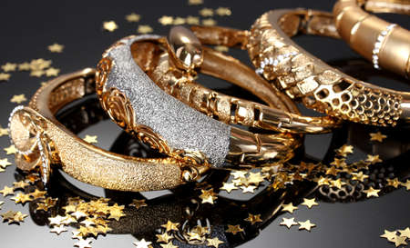 Beautiful golden bracelets on grey background photo