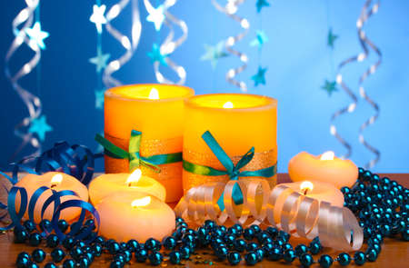 Beautiful candles, gifts and decor on wooden table on blue background Stock Photo - 13687614