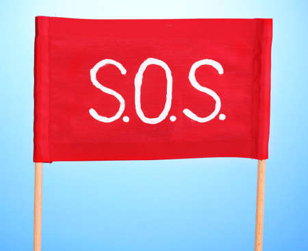 SOS signal written on red cloth on blue background Stock Photo - 13689097