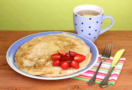 Stack of tasty pancakes on wooden table on green background Stock Photo - 13689121