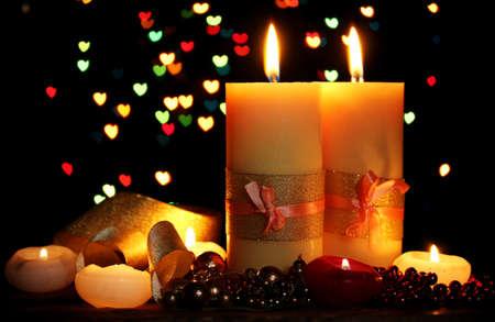 luz de velas: Hermosa vela y la decoraci�n en la mesa de madera sobre fondo brillante Foto de archivo