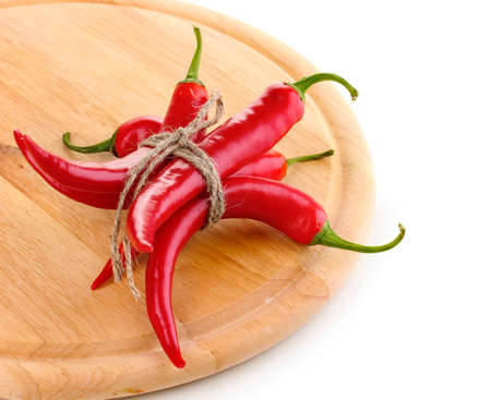 Red hot chili peppers tied with rope on wooden plank isolated on white photo