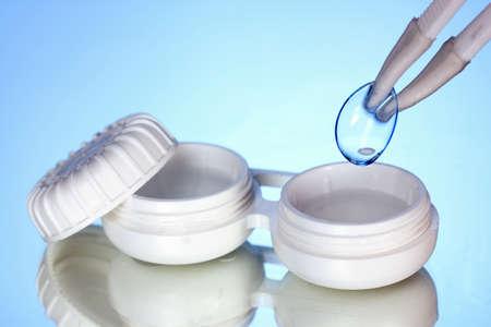pinzas: lentes de contacto en los contenedores y las pinzas sobre fondo azul Foto de archivo