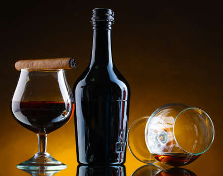 bottle and glasss of brandy and cigar on brown background photo