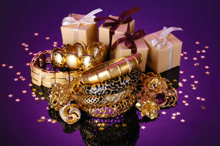 Beautiful golden jewelry and gifts on purple background photo
