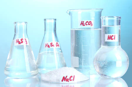 Test-tubes with various acids and chemicals  on blue background photo