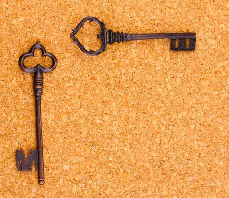 Two antique keys on cork background Stock Photo - 13810651
