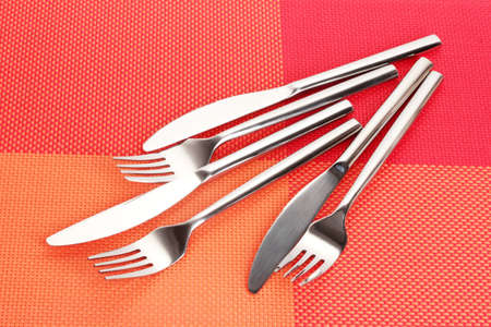 Forks and knives on a red tablecloth Stock Photo - 13810659