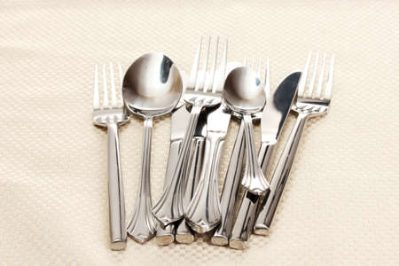 Forks, spoons and knives on a beige tablecloth Stock Photo - 13810440
