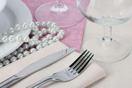 Table setting with fork, knife, plates, beads and napkin photo