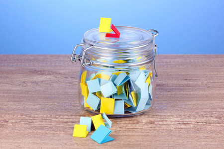 Pieces of paper for lottery in jar on wooden table on blue background photo