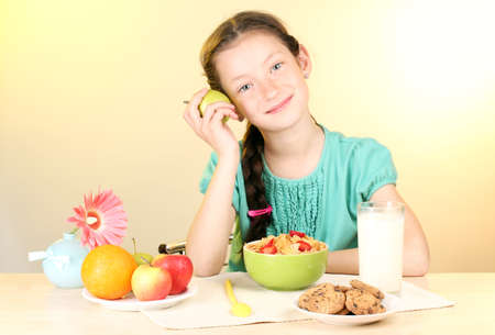 little beautiful girl have a breakfast on beige background photo