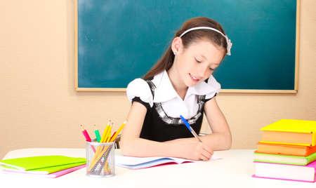 little schoolchild in classroom write in notebook Stock Photo - 14559176