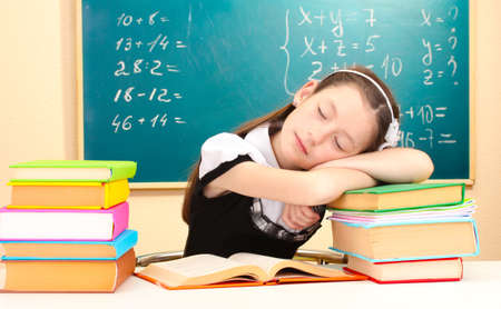 little schoolgirl sleep in classroom near blackboard photo