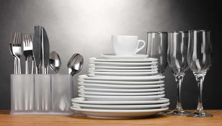Clean plates, glasses, cup and cutlery on wooden table on grey background photo