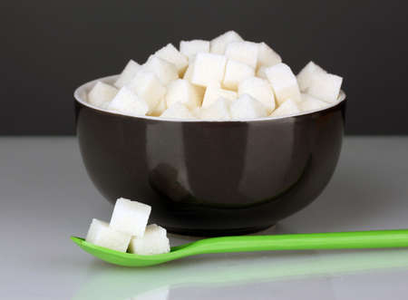Black bowl with white lump sugar with colorful spoon on grey background close-up photo