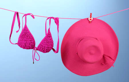 Women's bra swimsuit and hat hanging on a rope on blue background photo