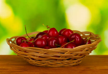 cherry in wicker bowl on wooden table on green background photo