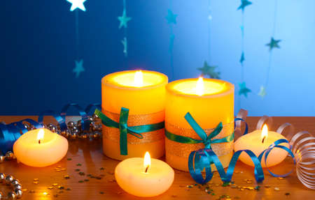 Beautiful candles, gifts and decor on wooden table on blue background Stock Photo - 13870853