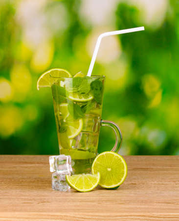 Glass of cocktail with lime and mint on wooden table green background