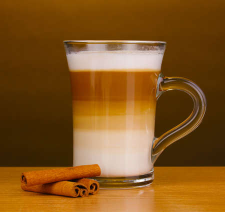 Fragrant cappuccino latte in glass cup and cinnamon on wooden table on brown background photo