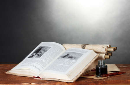 old books, scrolls, ink pen and inkwell on wooden table on grey background photo