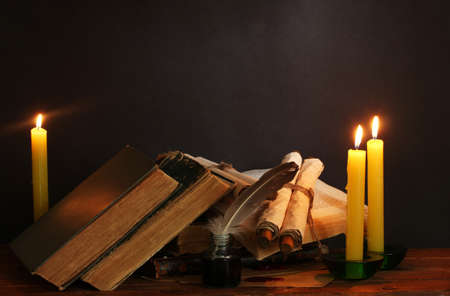 manuscripts: old books, scrolls, feather pen inkwell and candles on wooden table on brown background