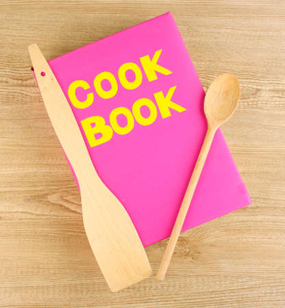Cookbook and kitchenware on wooden background photo